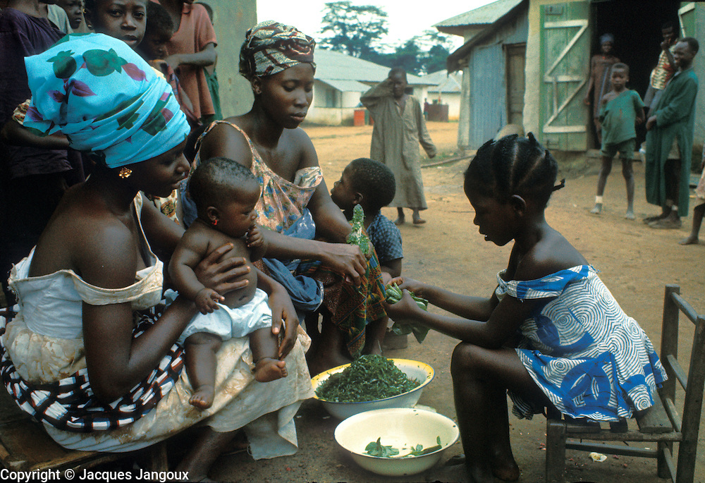 Women and girl preparing food in a village of the Kpelle tribe, Liberia, Africa