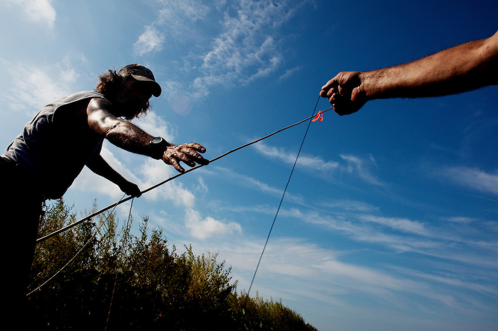 Julius Gaudet, 62, (R) hands Rebel a line while baiting a rod for alligator hunting near Shell Island, Louisiana on Saturday, September 19, 2009.