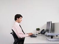 Male office worker using computer at desk in office