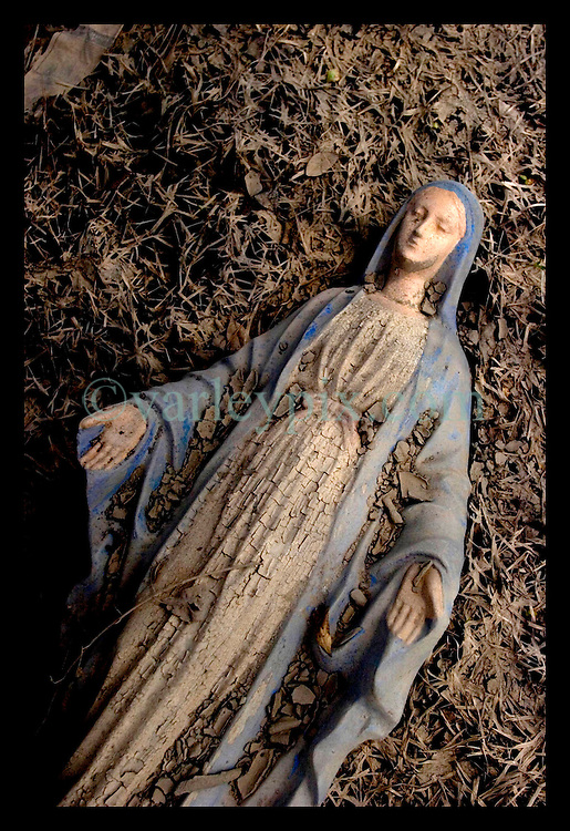 1st Oct, 2005. Hurricane Katrina aftermath, New Orleans, Louisiana. Lower 9th ward. The remnants of the lives of ordinary folks, now covered in mud as the flood waters recede. A statue of the Virgin Mary lies covered in mud with a beer can resting on her face.