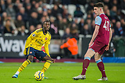 Nicolas Pepe (Arsenal) passes the ball past Declan Rice (West Ham) during the Premier League match between West Ham United and Arsenal at the London Stadium, London, England on 9 December 2019.