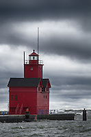 """Holland's """"Big Red"""" stands watch over the river as high winds send waves crashing into the outer piers"""