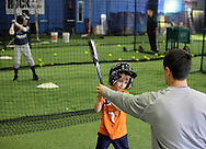 Chester, New York - An instructor works with a young baseball player in the batting cage during the first anniversary open house celebration at The Rock Sports Park on Nov. 12, 2011.