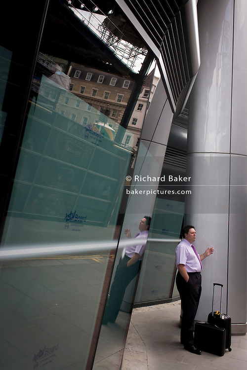 Businessman enjoys cigarette break beneath modern architecture on Walbrook, City of London.