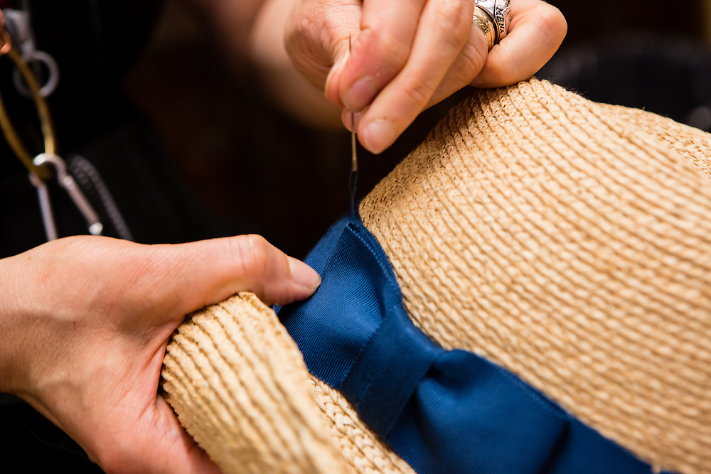 Hand sewing a bow onto the hatband of a straw hat.