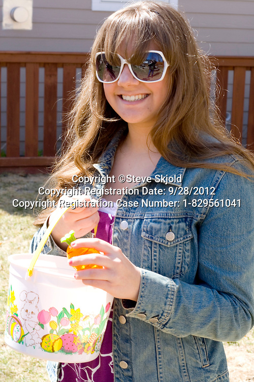 Happy female teen age 15 participating in family Easter egg hunt. St Paul Minnesota MN USA