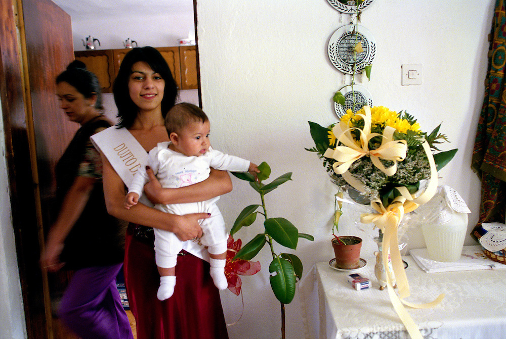 Mitra (16 from Macedonia) at home. She was the third place winner, and the only of the 5 winners to be from Skopje. She lives in a Roma neighbourhood on the outskirts of Skojpe, where majority of the population is Roma; there is even a Roma major. Here she is holding her friend?s baby and posing next to the flowers she received the night before, while her pregnant sister passes behind her. ?My sister wanted me to be in the competition, she wants me to be a model,? says Mitra who received a lot of support from her family.
