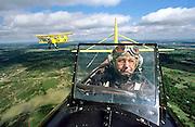 Elderly pilots fly bi-planes over Tulsa, OK.