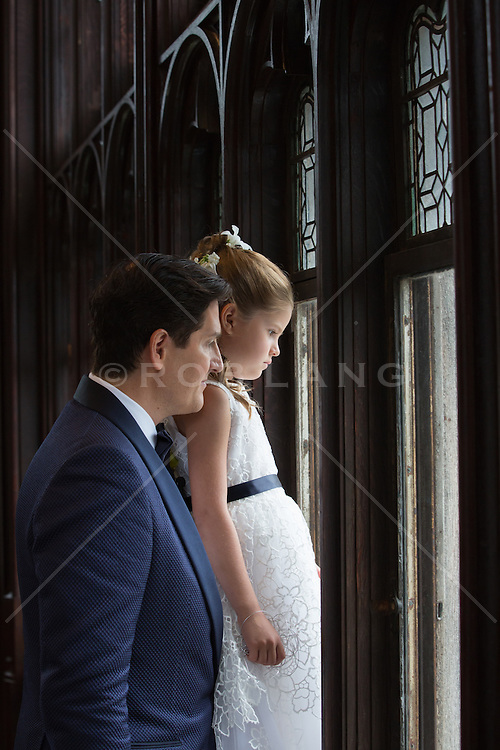 father and daughter looking out a large picture window during a wedding