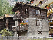 """A traditional wood house is preserved on Hinterdorfstrasse in Zermatt. The famous mountaineering and ski resort of Zermatt lies at 1620 meters or 5310 feet elevation at the head of Mattertal (Matter Valley) in Valais canton, Switzerland, the Pennine Alps, Europe. Zermatt bars combustion-engine cars to help preserve small village atmosphere and prevent air pollution. The German word matten means """"alpine meadows."""" Most visitors reach Zermatt by cog railway train from the nearby town of Täsch (Zermatt shuttle). Trains also depart for Zermatt from farther down the valley at Visp and Brig on the main Swiss rail network. Hike the High Route (Chamonix-Zermatt Haute Route) for exceptional mountain scenery."""