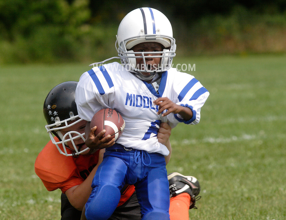 Middletown, NY - A Middletown players runs with the football as a Marlboro defender tries to make the tackle during an Orange County Youth Football League game at Watts Park  on Sept. 9, 2007.