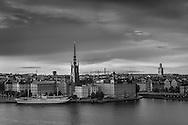 Riddarholmen i skymning med uppklarnande efter häftig regnskur vid Riddarfjärden i Stockholm i svartvitt.