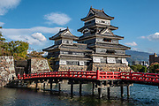 """Matsumoto Castle can best be admired by its red bridge. The castle was built from 1592-1614 in Matsumoto, Nagano Prefecture, Japan. Matsumoto Castle is a """"hirajiro"""" - a castle built on plains rather than on a hill or mountain, in Matsumoto. Matsumotojo's main castle keep and its smaller, second donjon were built from 1592 to 1614, well-fortified as peace was not yet fully achieved at the time. In 1635, when military threats had ceased, a third, barely defended turret and another for moon viewing were added to the castle. Interesting features of the castle include steep wooden stairs, openings to drop stones onto invaders, openings for archers, as well as an observation deck at the top, sixth floor of the main keep with views over the Matsumoto city."""