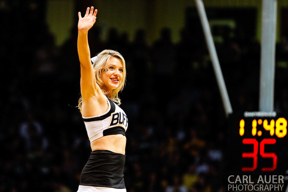November 13th, 2013:  A Colorado Buffaloes cheerleader waves to the crowd during a time out in the NCAA Basketball game between the University of Wyoming Cowboys and the University of Colorado Buffaloes at the Coors Events Center in Boulder, Colorado