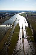 Nederland, Limburg, Gemeente Venlo, 07-03-2010; Sluis en stuwcomplex Belfeld, aangelegd in het kader van de kanalisatie van de Maas in de jaren 1918 - 1929. In de sluis wordt een schip geschut. Bij hoog water van de Maas kan het sluiscomplex overstromen, alle gebouwen staan op kolommen. .De stuw bestaat uit twee delen: schuiven die opgehesen kunnen worden (Stoney gedeelte) en schuiven op jukken (onder water, rechts, het Poiree gedeelte). Bij hoogwater worden de stuw 'gestreken' alle schuiven zijn dan omhoog respectievelijke verwijderd, scheepvaart is dan mogelijk door het geheel vrije stuwopening. .Lock and weir complex Belfeld, built in the context of the canalization of the Meuse in the years 1918 to 1929. A ship is locked through. .In case of high waters, the locks will be flooded, therefore the buildings are build on columns. The weir consists of two parts: slides that can be lifted (Stoney part) and slides on yokes (underwater, right, the Poirée part). At extreme high waters, the wie is 'lifted', all sliders are up respectively removed, shipping is possible through the completely free weir opening..luchtfoto (toeslag), aerial photo (additional fee required).foto/photo Siebe Swart