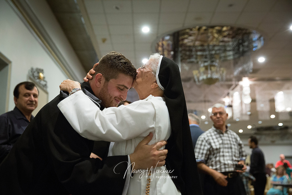 Newly ordained Father David Stephen receives a kiss from his aunt during a reception at St. Peter Chaldean Catholic Cathedral in El Cajon, Calif., Aug. 14, 2015. She traveled from Iraq to be with the family for his ordination. (Nancy Wiechec for ONE magazine)