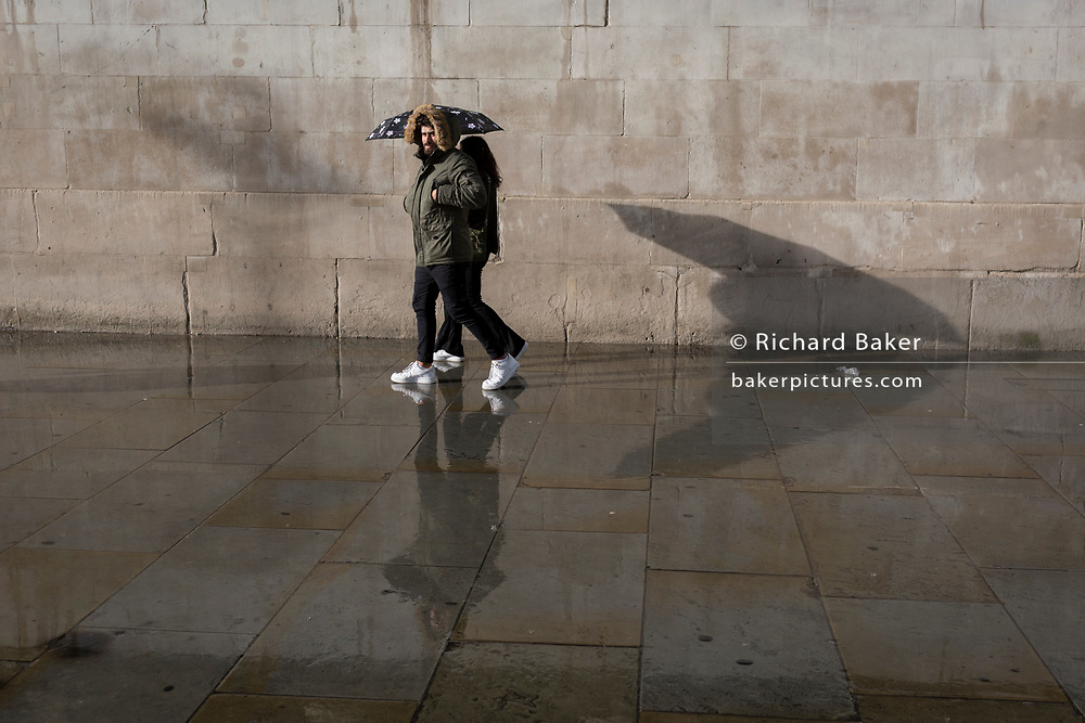 Pedestrians enjoy a brighter afternoon again after an autumnal downpour in Trafalgar Square in central London, on 1st October 2019, in London, England.