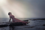 a woman in a pink dress is lying on stones at the sea