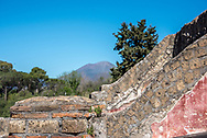Exposed wall layers at Pompeii with Mount Vesuvius in the background. Different sized bricks are visible with some remaining plaster painted red.