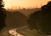 UNITED KINGDOM, London: 13 May 2015 A deer crosses a glistening road in Richmond Park, London this morning during sunrise. Although it was a cold start to the day, temperatures are set to get up to 20C. Rick Findler  / Story Picture Agency