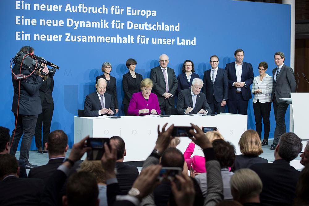 12 MAR 2018, BERLIN/GERMANY:<br /> Horst Seehofer (L), CSU, desig. Bundesinnenminister, Angela Merkel (M), CDU, Bundeskanzlerin, und Olaf Scholz (R), SPD, desig. Bundesfinanzminister, in der zweiten Reihe: drei Damen des Protokolls, Volker Kauder, CDU, CDU/CSU Fraktionsvorsitzender, Andrea Nahles, SPD Fraktionsvorsitzende, Alexander Dobrindt, Vorsitzender der CSU Landesgruppe, Lars Klingbeil, SPD Generalsekretaer, Annegret Kramp-Karrenbauer, CDU Generalsekretaerin, und Andreas Scheuer, CSU Generalsekretaer, Unterzeichnung des Koalitionsvertrages der CDU/CSU und SPD, Paul-Loebe-Haus, Deutscher Bundestag<br /> IMAGE: 20180312-02-012