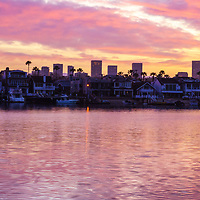 Newport Beach California skyline sunrise panorama photo with Fashion Island office buildings, Balboa Island homes, and Newport Harbor. Newport Beach is coastal city in Orange County Southern California in the United States of America. Panorama photo ratio is 1:3. Copyright ⓒ 2017 Paul Velgos with All Rights Reserved.