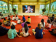 13 DECEMBER 2017 - BANGKOK, THAILAND:  People watch a replay of the royal cremation in the Royal Crematorium on Sanam Luang in Bangkok. The crematorium was used for the funeral of Bhumibol Adulyadej, the Late King of Thailand. He was cremated on 26 October 2017. The crematorium is open to visitors until 31 December 2017. It will be torn down early in 2018. More than 3 million people have visited the crematorium since it opened to the public after the cremation of the King.    PHOTO BY JACK KURTZ