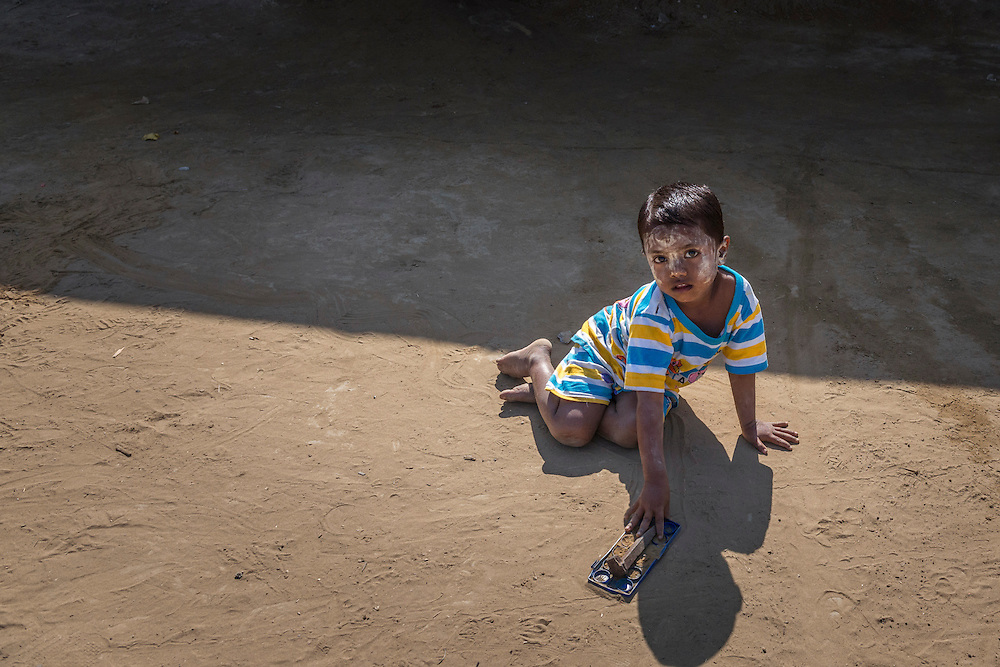 A child plays with an empty paint box at the Badupa Camp near Sittwe. 2015-02-05.