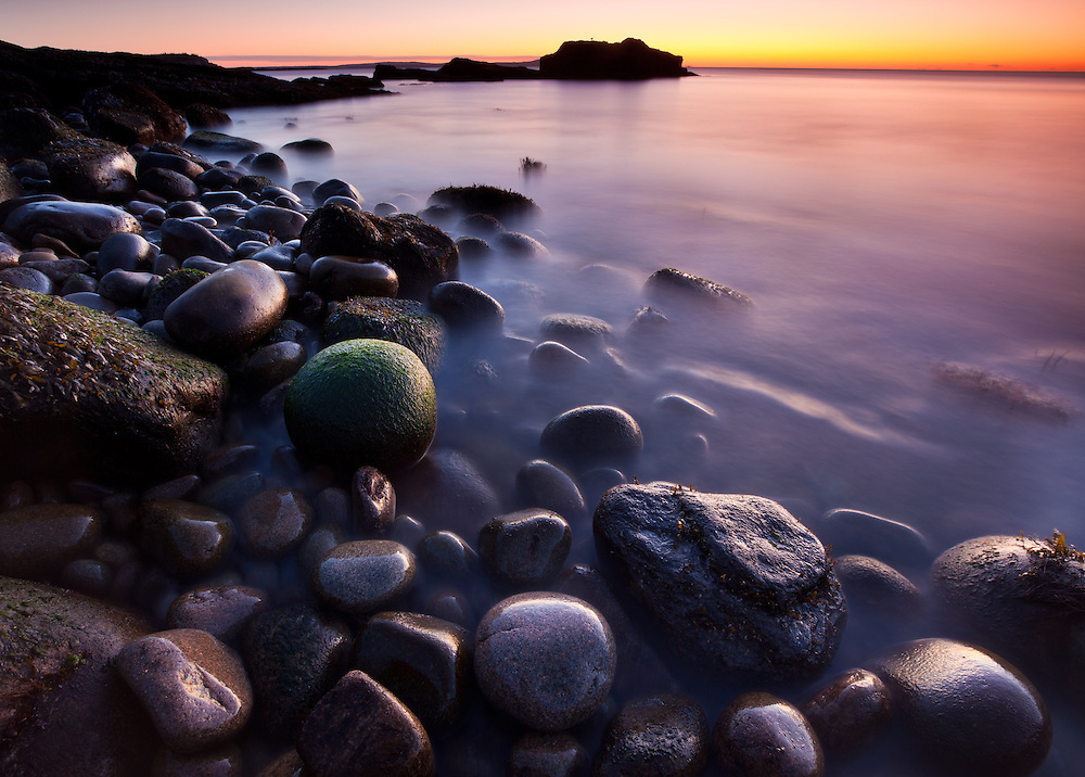 a colorful sky just before sunrise on a cobble beach in Acadia National Park in Maine