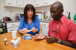Elderly black man with white woman carer discussing medication