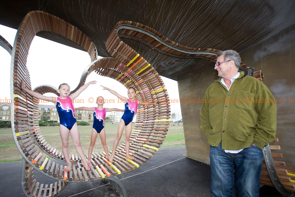 JAMES BOARDMAN / 07967642437.Gordon Roddick looks on as gymnasts from Arun Gymnastics Club in West Sussex limber up in a seafront shelter which forms part of Littlehampton Long Bench - the longest bench in Britain. The new 324 metre bench, complete with two iconic shelters, was funded through a £450,000 grant from the Sea Change Programme run by the commission for Architecture and the Built Environment [CABE] and a private donation of £100,000 from Mr Roddick as a tribute to his late wife Anita, founder of the Bodyshop.