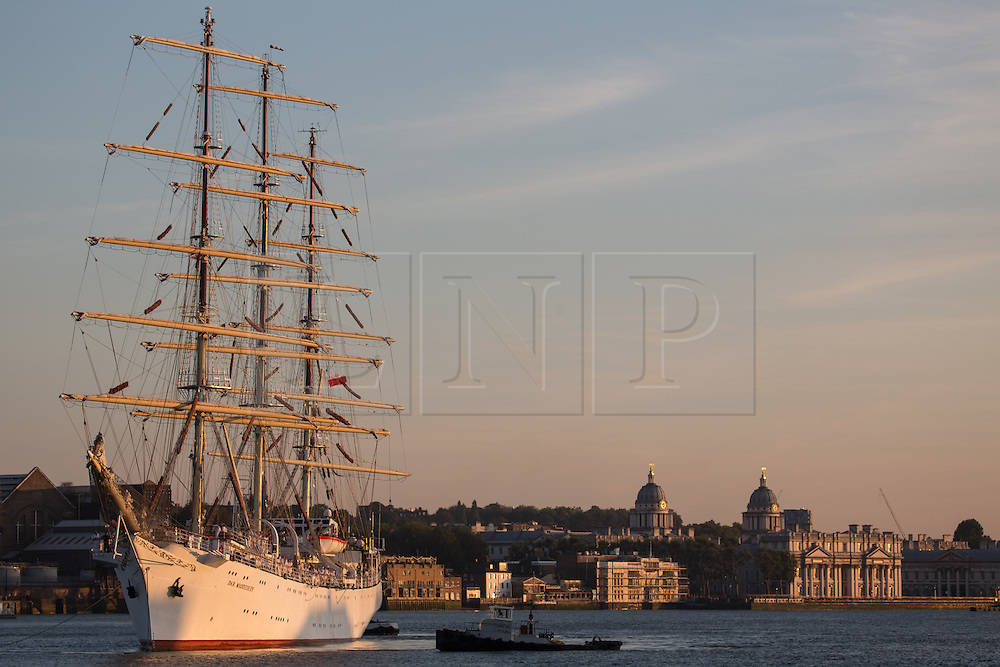 © Licensed to London News Pictures. 03/09/2014. Tall ship pictured with the Old Royal Naval College in Greenwich behind. The huge tall ship Dar Mlodziezy arrived in London the evening of September 3rd in readiness for this weekend's Royal Greenwich Tall Ships Festival. Reckoned to be the largest tall ship on the Thames for 25 years, the 108-metre-long Class A ship arrived in London shortly before sunset. She will be joined by approximately 50 other ships for the regatta this weekend which is expected to draw over a million people. All of the ships will leave in a Parade of Sail on September 9th. It is the biggest Tall Ships event on the Thames since the Tall Ships Race of 1989. Credit : Rob Powell/LNP