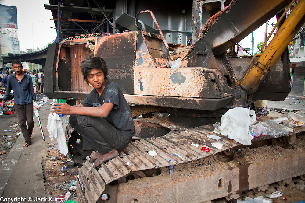 18 MAY 2010 - BANGKOK, THAILAND: An anti government protester sits on a digger he helped destroy with fire Monday in Din Daeng Intersection in Bangkok Tuesday. The intersection has been under periodic sniper fire from unidentified snipers near Thai military lines. Violent unrest continued in Bangkok again Tuesday nearly a week after Thai troops started firing on protesters and Bangkok residents took to the streets in violent protest against the government. Tuesday was not as violent as previous days however. Although protesters continued to set up roadblocks and flaming tire barricades across parts of the city, there was not as much gunfire from the government lines. The most active protesters were at the Din Daeng Intersection about a mile from the Red Shirts' Ratchaprasong camp.  PHOTO BY JACK KURTZ