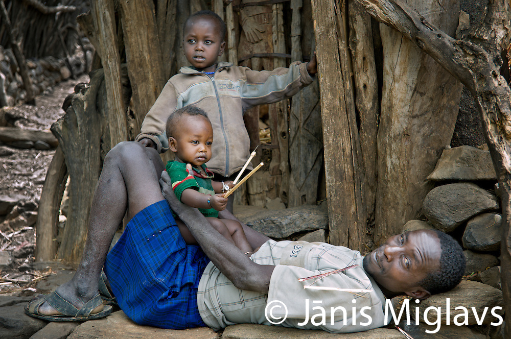 While laying on some flat stones, a father in blue shorts plays with his two children in  in Busso Village, Konso tribe, Omo region, Ethiopia. The hand and legs from a Waka can be seen in the background.
