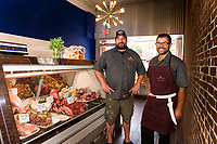 Kevin Halligan and Tom Rendall stock the cases with meats and seafood for opening day at Local Provisions on Main Street Saturday morning.  (Karen Bobotas/for the Laconia Daily Sun)