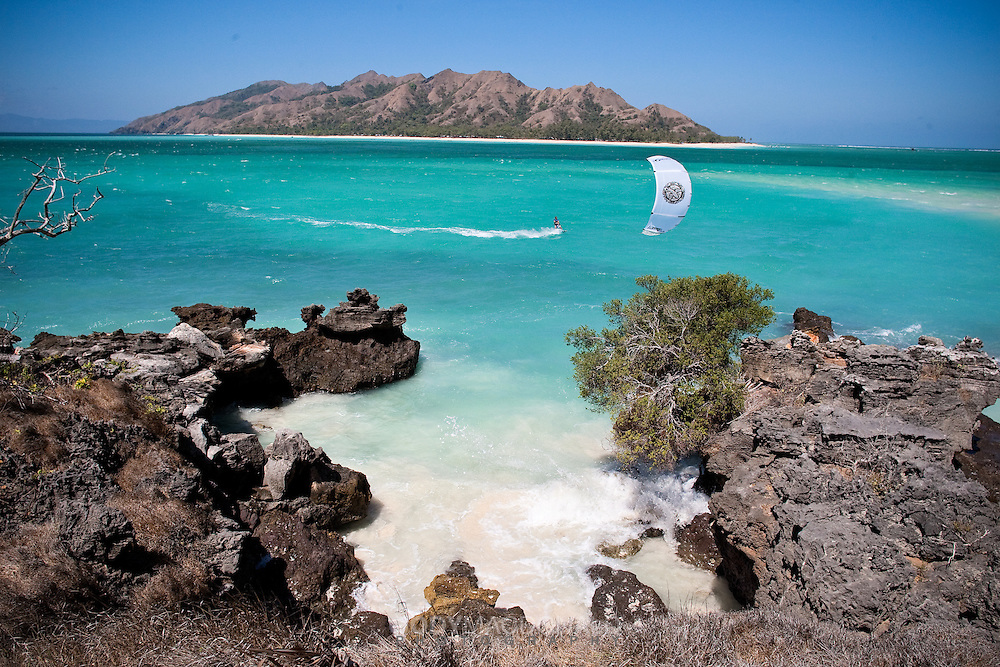 kitesurfer glides across lagoon in outer reaches of Indonesia off the south coast of Sumba