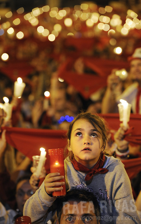 "Revellers take part in the ""Pobre de Mi"" celebration, in front of the Pamplona Town Hall, where they light candles, wave their red scarves and sing farewell songs, to end the San Fermin festivities in Pamplona, north of Spain, on July 14, 2008. Revellers light candles and wave their red scarves to say good bye to the San Fermin festivities, during the celebration of the ""Pobre de Mi!"" (poor me!), on July 14, 2008, in the northern Spanish city of Pamplona."