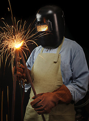 Welder torching a piece of steel against a black background
