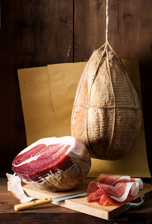 culaccia lombarda ham hanging,another half cut , and slices on a chopping board with a knife aside