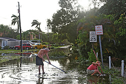 Siena Sanderson and her father, Glenn Sanderson, work to clear a drain in front of their Fort Lauderdale home on Monday, September 11, 2017, after Hurricane Irma blew through South Florida. Siena Sanderson, who lives in Taos, N.M., flew in last Wednesday to help her parents, who are both in their 90s. Photo by Amy Beth Bennett/Sun Sentinel/TNS/ABACAPRESS.COM