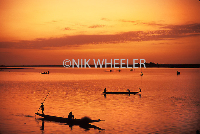 Wooden boats at sunset at the confluence of the Bani and Niger Rivers in the Niger Delta at Mopti in Niger, West Africa.