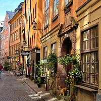 """Number 37 Österlånggatan Street in Stockholm, Sweden <br /> Österlånggatan is a quaint, cobblestone street running through the eastern side of Old Town.  During the 13th century, this was the major road outside of the cities walls facing Strömen Bay. It lost its prominence in the 17th century when a block of land was created to form Skeppsborn and the adjoining quay. Today, Österlånggatan is lined with buildings dating back centuries. A good example is Number 37 in the foreground. Part of this building is from medieval times while most was constructed during the 17th and 18th centuries.  The gable stone above the door reads in Dutch: """"When luck stands by one have a lot of friends but when luck turns where are they then?"""""""