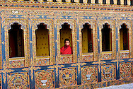 A young Bhutanese monk looks out a window of Tango Lakkhang monastery, Bhutan, Asia