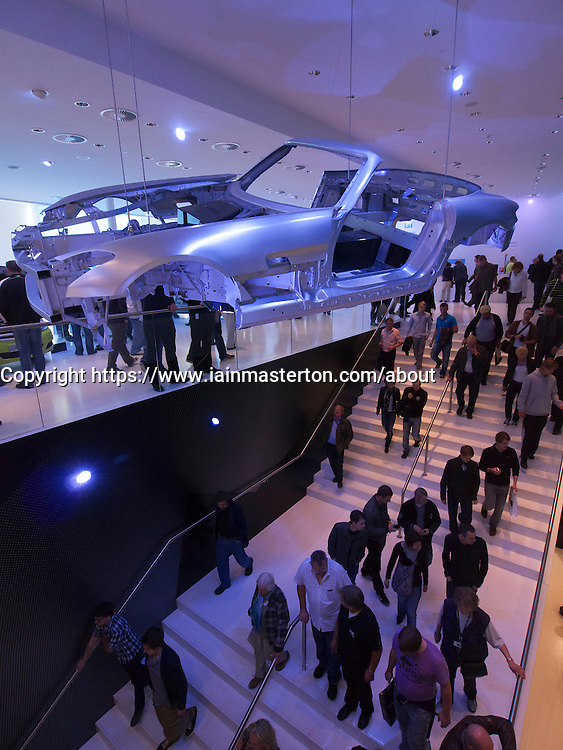 Mercedes car chassis hangs above visitors to Frankfurt Motor Show or IAA 2011 Germany