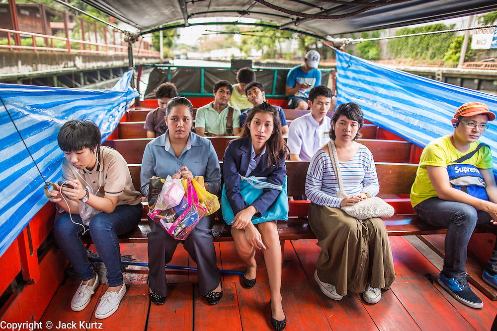 14 NOVEMBER 2012 - BANGKOK, THAILAND: Passengers on a khlong boat on Khlong Saen Saeb in Bangkok. Bangkok used to be criss crossed by canals (called Khlongs in Thai) but most have been filled in and paved over. Khlong Saen Saeb is one of the few remaining khlongs in Bangkok with regular passenger boat service. Boats and ships play an important in daily life in Bangkok. Thousands of people commute to work daily on the Chao Phraya Express Boats and fast boats that ply Khlong Saen Saeb. Boats are used to haul commodities through the city to deep water ports for export.      PHOTO BY JACK KURTZ
