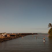 Stand Up Paddle Boarders gently make their way down the river toward the ocean on Maui's north shore, Hawaii