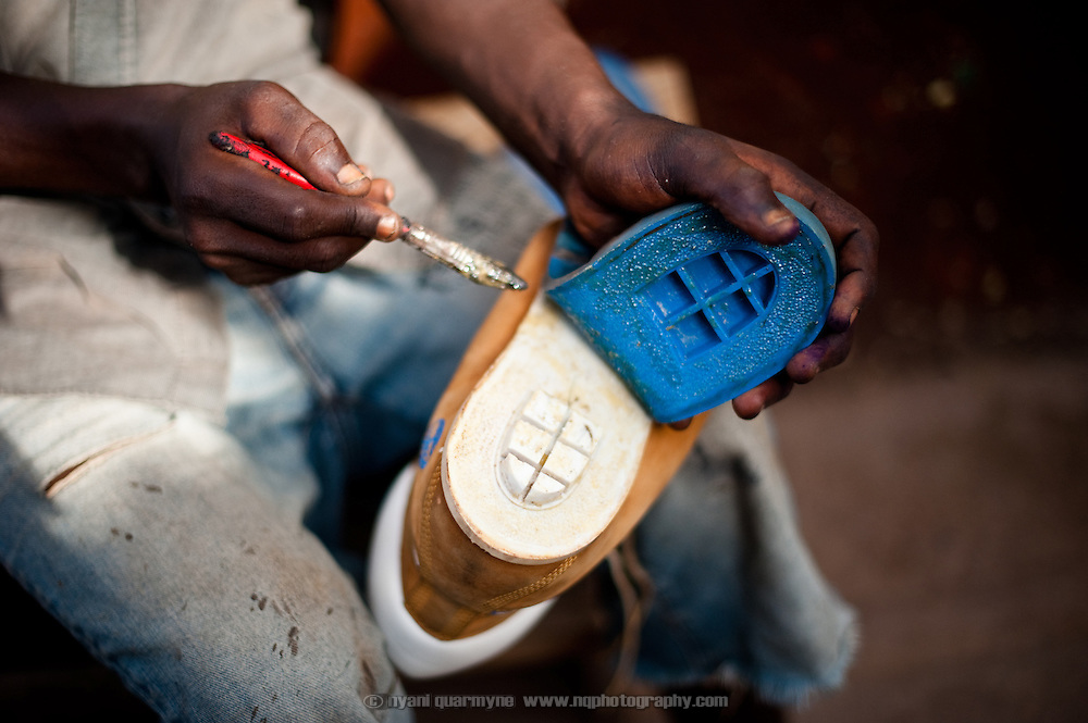 Isaac Yeboah in Nima, a densely populated area of Accra, Ghana. He took up shoe repair three months before this photo was taken afterthe construction project he was working on ended.