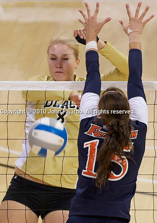 Haleigh Hampton hits past the block of Fullerton's Torrie Brown(R) in the Big West Conference match at the Walter Pyramid, Long Beach, Calif., Saturday, Sept. 25, 2010.  The 49ers win in three sets, 25-16, 25-19, 25-18.