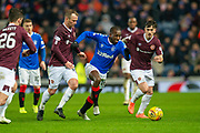 Glen Kamara (#18) of Rangers FC runs between Glenn Whelan (#12) of Heart of Midlothian FC and Jamie Walker (#10) of Heart of Midlothian FC during the Ladbrokes Scottish Premiership match between Rangers FC and Heart of Midlothian FC at Ibrox Park, Glasgow, Scotland on 1 December 2019.