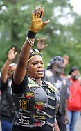 Sister Sohjah raises her hand in prayer before the start of a Moving in Peace motorcade thru all of Camden's neighborhoods to recognize and honor the victims of violence in the city Saturday, August 12, 2017 at Farnham Park in Camden, New Jersey. (WILLIAM THOMAS CAIN / For The Philadelphia Inquirer)